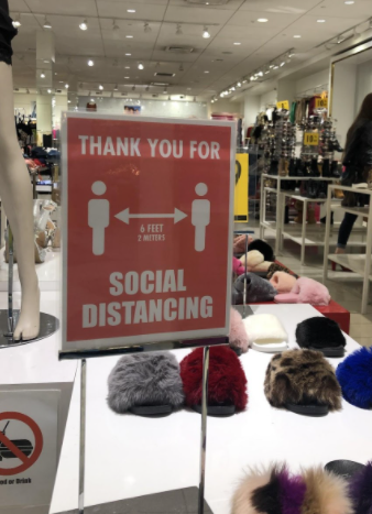 Social distancing reminder sign at a local store