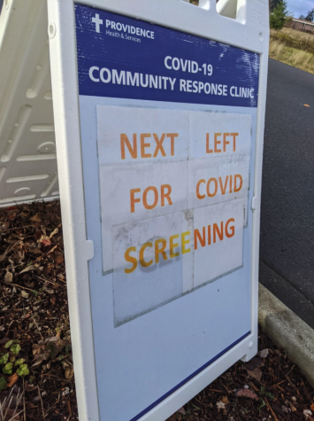 The main sign on the curb welcoming people for COVID screening
