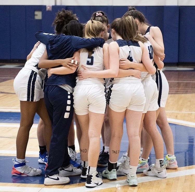2020 varsity girls basketball team huddling before a big game. Photo by John O'Leary.