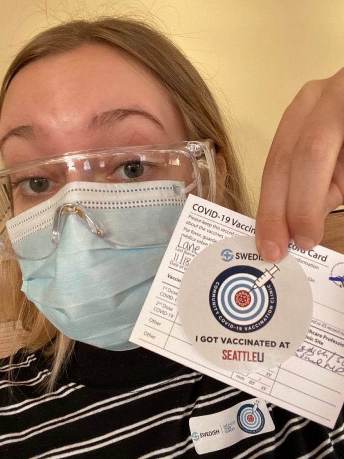 Audrey Lane poses for a selfie with her vaccine paperwork from the Seattle U vaccination site.